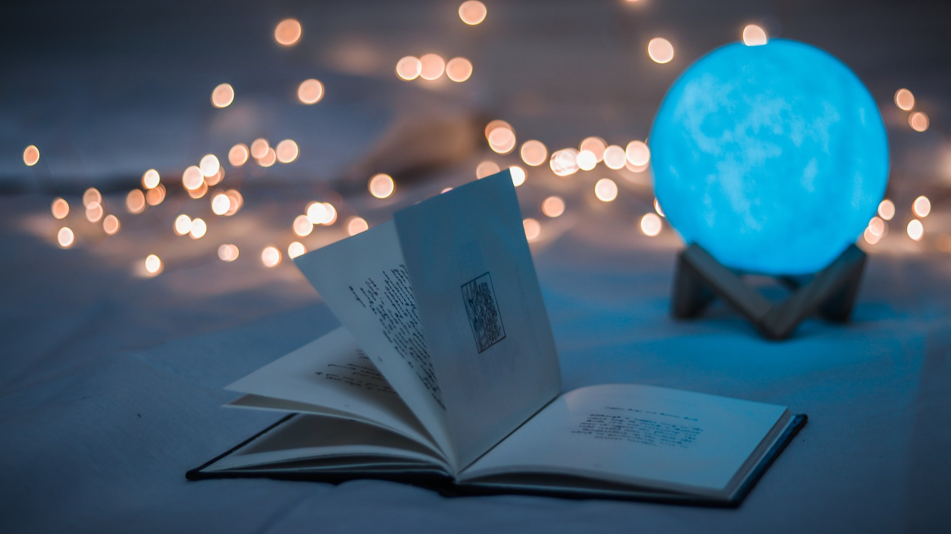 Opened book beside crystal ball