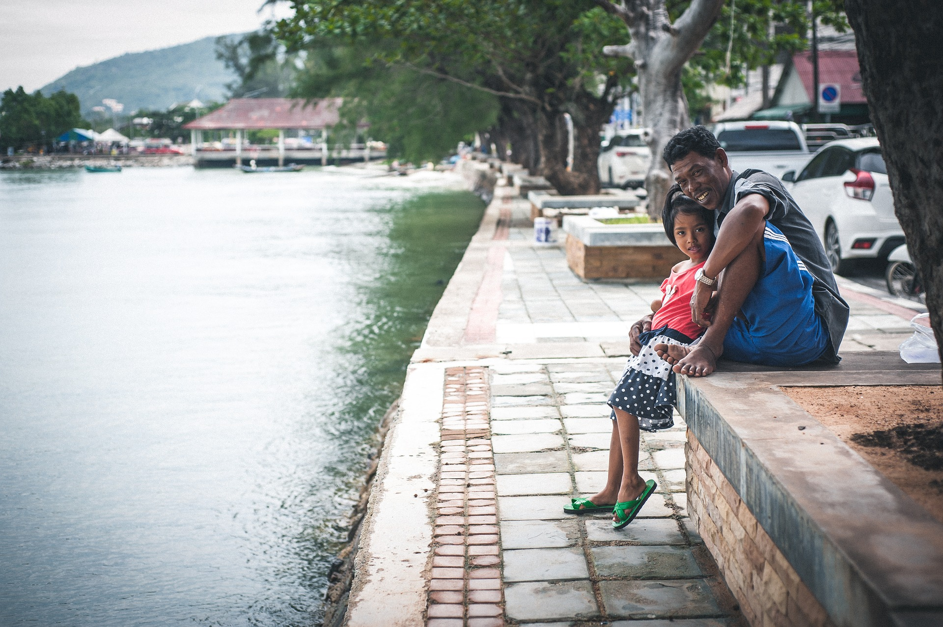 Thai family sitting on a river bank