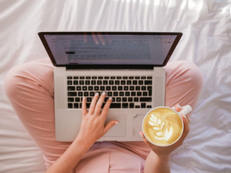 person using laptop and holding cup of coffee